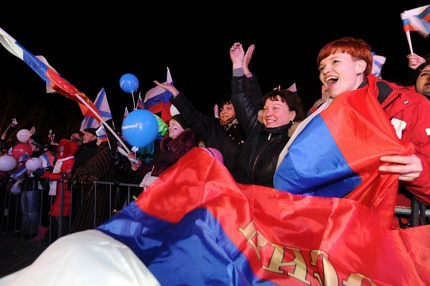Pro-Russian Crimeans celebrate in Sevastopol on March 16, 2014, after partial votes showed that about 95.5 per cent of voters in Ukraine's Crimea region supported union with Russia. -- PHOTO: AFP