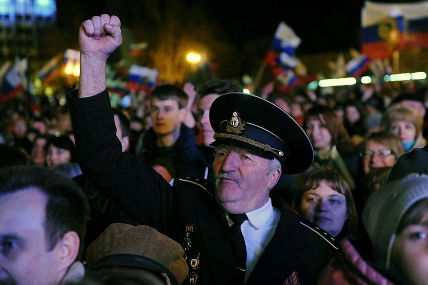 Pro-Russian Crimeans celebrate in Sevastopol on March 16, 2014, after partial showed that about 95.5 per cent of voters in Ukraine's Crimea region supported union with Russia. -- PHOTO: AFP