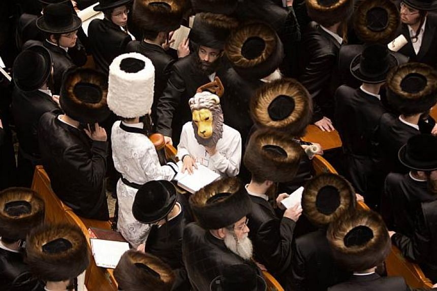 Ultra-Orthodox Jews read the Book of Esther near dressed up children at a synagogue in Jerusalem on March 16, 2014 during the feast of Purim. -- PHOTO: AFP