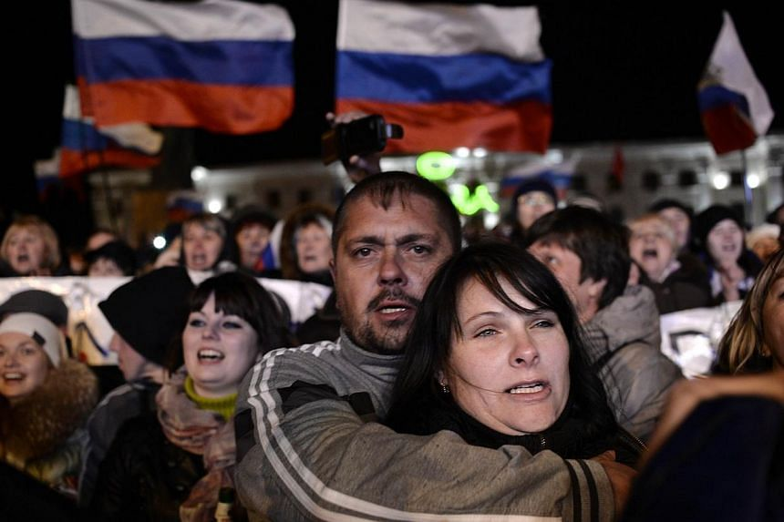 People sing the Russian national anthem as they celebrate in Simferopol's Lenin Square on March 16, 2014 after exit polls showed that about 95.5 percent of voters in Ukraine's Crimea region supported union with Russia.Russian media on Monday, M