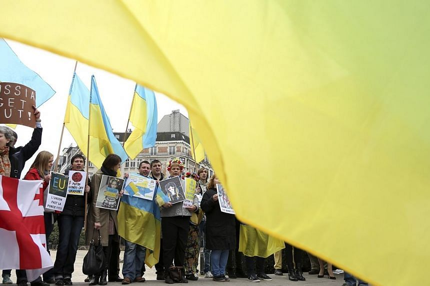 Ukrainians living in Belgium hold Ukrainian flags and chant slogans against Russian President Vladimir Putin during a protest against Russia's incursion into Crimea, outside a meeting of European Union foreign ministers in Brussels March 17, 2014.&nb
