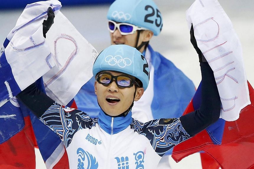 Viktor Ahn (front) and Vladimir Grigorev of the winning Russian team hold up their national flag after the men's 5,000 metres short track speed skating final relay race at the Iceberg Skating Palace in the Sochi 2014 Winter Olympic Games February 21,