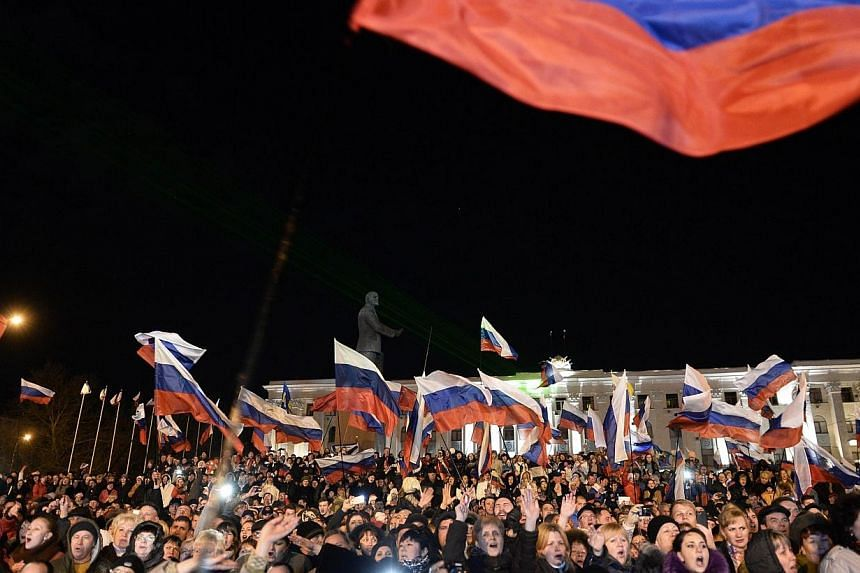 Pro-Russian Crimeans gather to celebrate in Simferopol's Lenin Square on March 16, 2014 after exit polls showed that about 93 percent of voters in Ukraine's Crimea region supported union with Russia. Crimea's regional assembly on Monday, March 1