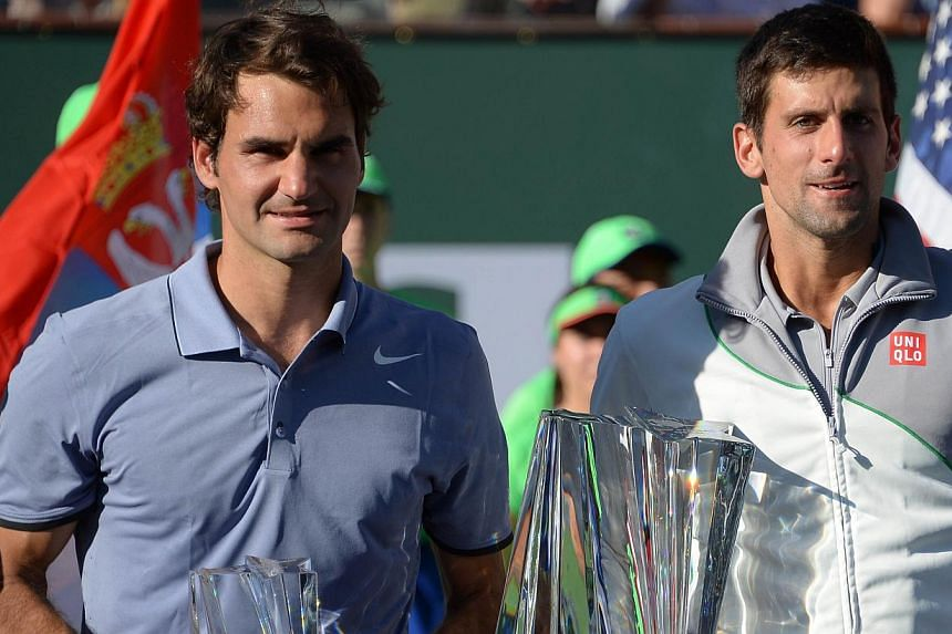 Switzerland's Roger Federer (left) and Serbia's Novak Djokovic pose with trophies during men's final match of the BNP Paribas Open at Indian Wells Tennis Garden in California on March 16, 2014. -- PHOTO: AFP