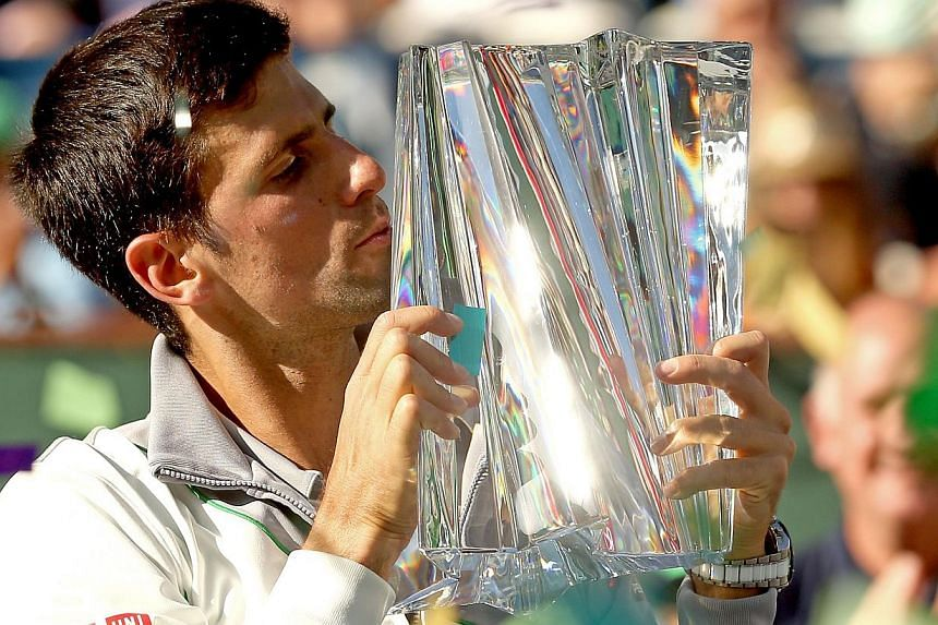 Novak Djokovic of Serbia poses for photographers after defeating Roger Federer of Switzerland during the final of the BNP Parabas Open at the Indian Wells Tennis Garden in California, on March 16, 2014. -- PHOTO: AFP