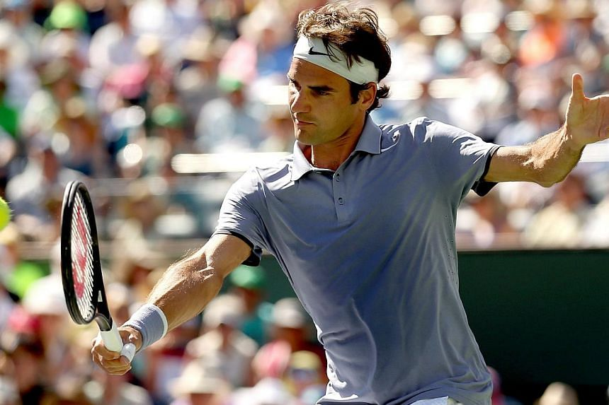 Roger Federer of Switzerland returns a shot to Novak Djokovic of Serbia during the final of the BNP Parabas Open at the Indian Wells Tennis Garden in California, on March 16, 2014. -- PHOTO: AFP
