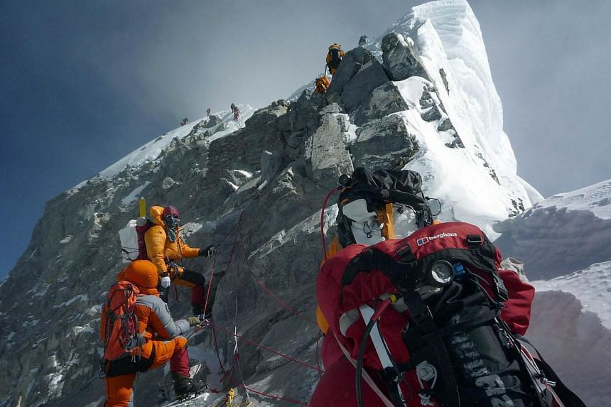 In this May 19, 2009, file photograph, unidentified mountaineers walk past the Hillary Step while pushing for the summit of Mount Everest as they climb the south face from Nepal.Nepal may install ladders on Mount Everest's Hillary Step, the fin