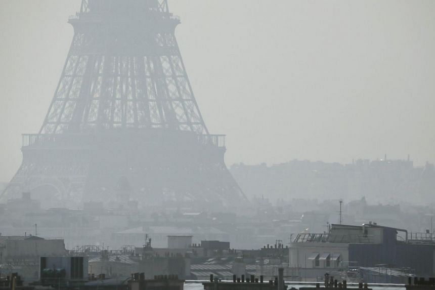 A view of the Eiffel Tower seen through thick smog, on March 14, 2014, in Paris. Paris on Monday resorted to drastic measures to curb soaring pollution levels by forcing all cars with number plates ending in even numbers off the road for the fir