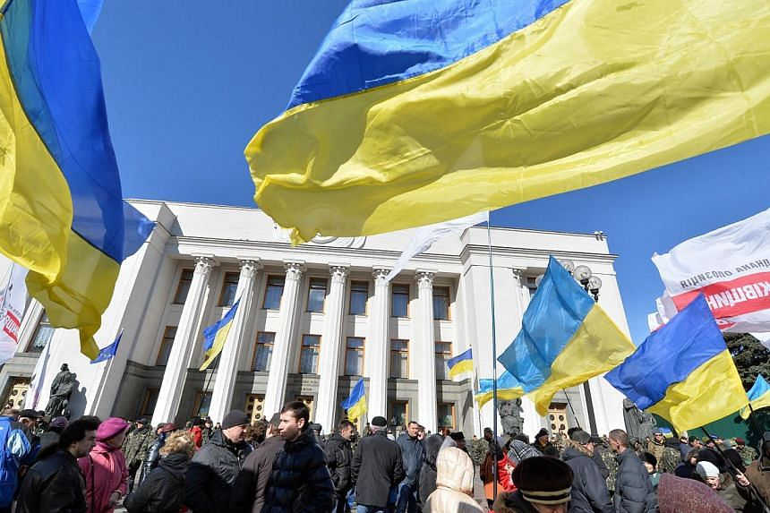 """People hold Ukrainian flags as they gather in front of the Parliament in Kiev on March 17, 2014.Ukraine's Foreign Minister denounced Russian """"provocations"""" on Monday, warning of a troop build-up on the border and the presence of """"political tour"""