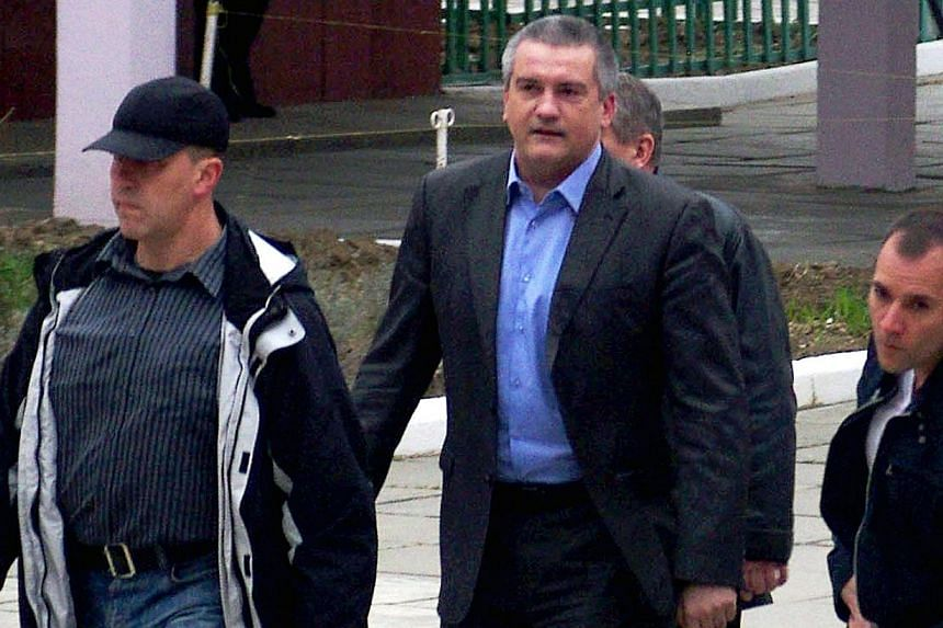 Crimea's Prime Minister Sergiy Aksyonov (centre) leaves the polling station after voting in a a local school on March 16, 2014, in Simferopol.Crimea's separatist leader on Monday said Russia had sent the autonomous republic the equivalent of ne