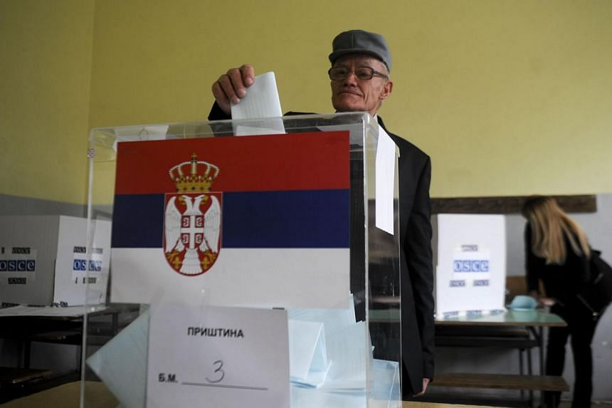 A Serbian voter casts her ballot at a polling station in Belgrade on March 16, 2014. -- PHOTO: AFP