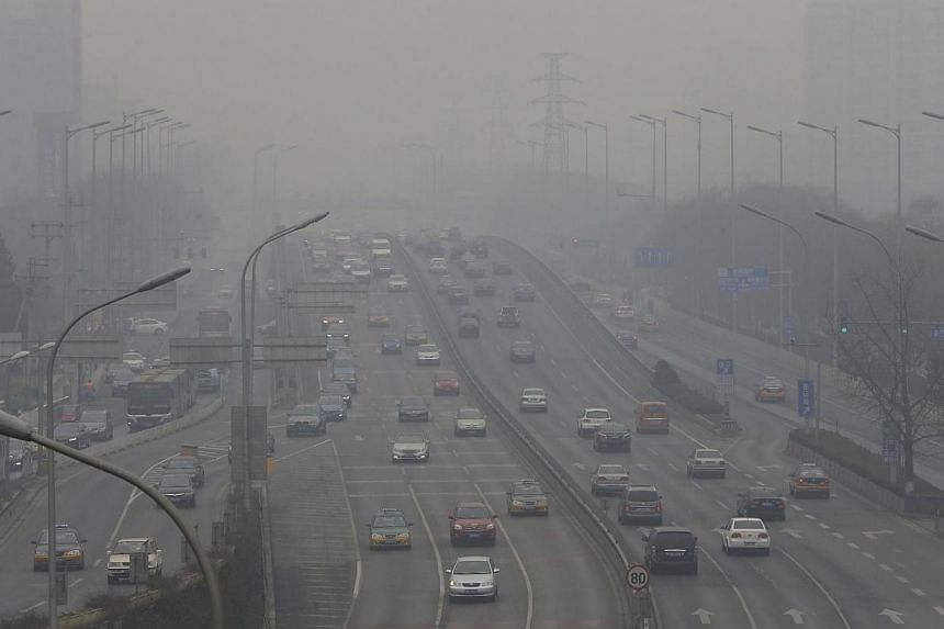 Cars drive on the second ring road amid the heavy haze in Beijing February 21, 2014. A state-owned Chinese insurer will offer residents of Beijing insurance cover against health risks caused by air pollution, promising to pay out 1,500 yuan (S$307) t