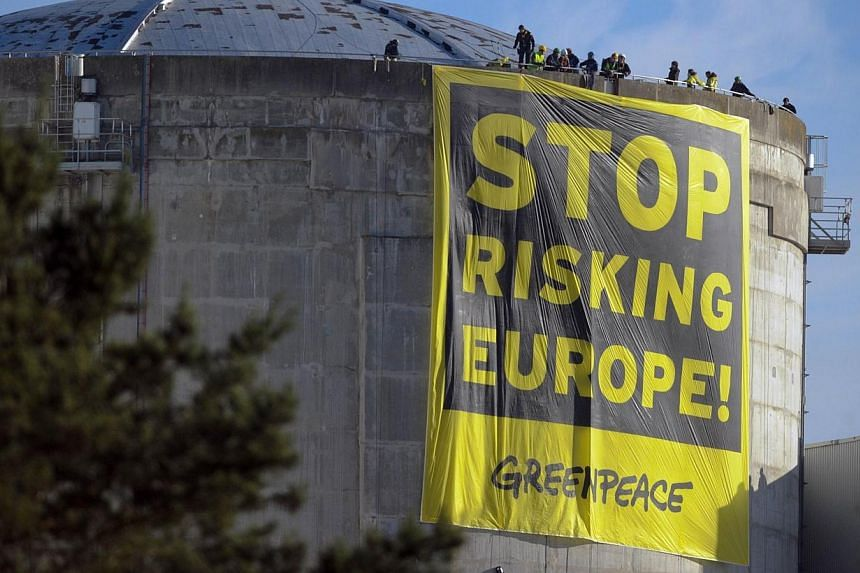 """Militants of Greenpeace deploy a banner reading """"Stop risking Europe"""" on a reactor of the nuclear power plant of Fessenheim on March 18, 2014.Environmental activists from Greenpeace entered a nuclear power plant operated by EDF in Fessenheim, e"""