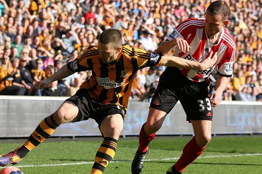 Hull City's English striker Matt Fryatt (left) tries to hold off Sunderland's English forward Lee Cattermole (right) during the English FA Cup quarter-final match between Hull City and Sunderland at the KC Stadium in Kingston upon Hull, north- east E