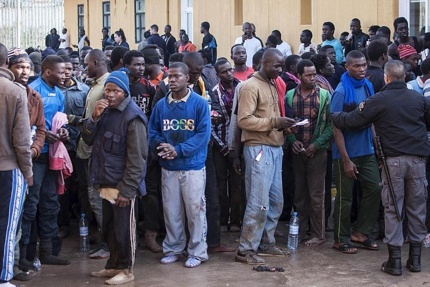Illegal migrants stand at the Centre for Temporary Stay of Immigrants (CETI) on the north African Spanish enclave of Melilla on March 18, 2014. About 500 African migrants stormed over the border fence from Morocco into the Spanish territory of Melill