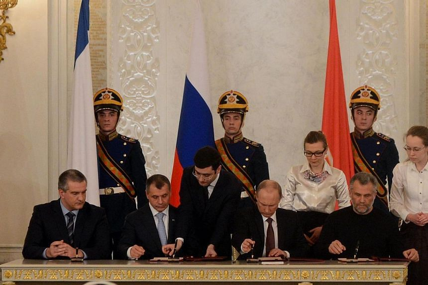 Russia's President Vladimir Putin (second from right), Crimean Prime Minister Sergei Aksyonov (left), Crimean parliament speaker Vladimir Konstantionov (second from left) and Alexei Chaly, Sevastopol's new de facto mayor (right), sign a treaty on the