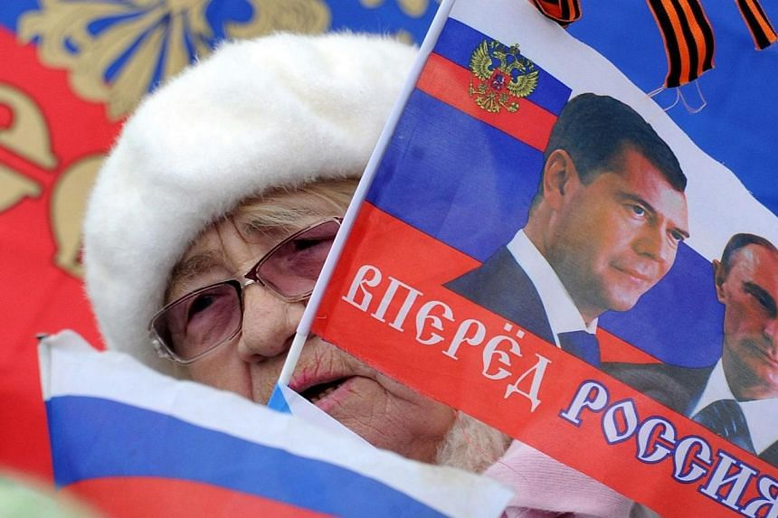 A woman holds a flag depicting Russian President Vladimir Putin and Russian Prime Minister Dmitriy Medvedev during a rally in Sevastopol on March 17, 2014. President Vladimir Putin on Tuesday, March 18, 2014 took the first steps to absorb the Uk