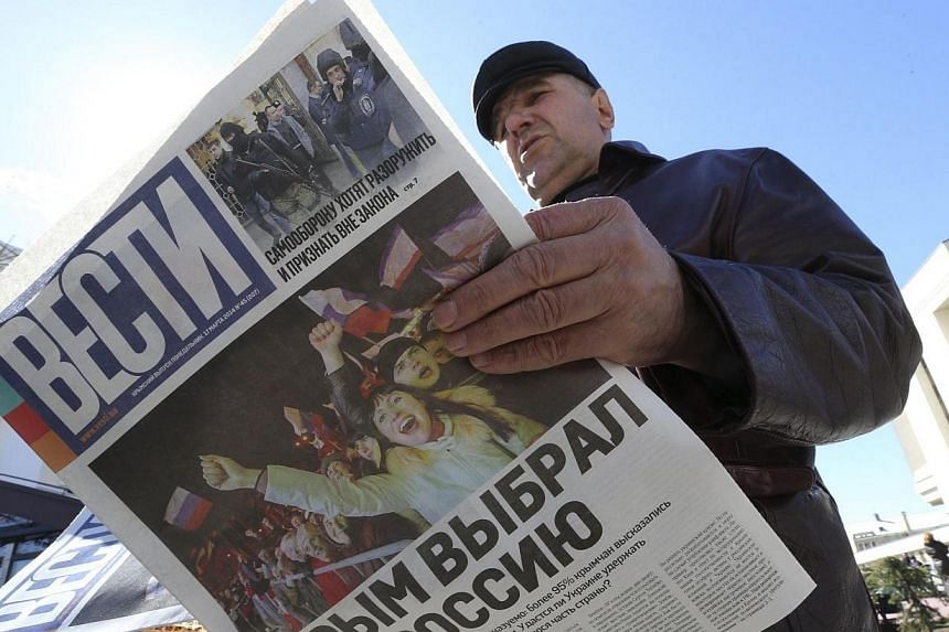 """A man reads a free newspaper with the headline """"Crimea chooses Russia"""" on a street in Simferopol on March 17, 2014. Ukraine will never recognise Russia's annexation of Crimea, a spokesman for the foreign ministry in Kiev said Tuesday, March 18, 2014,"""