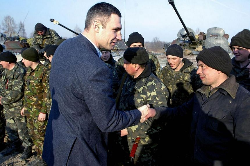 Leader of Ukrainian UDAR (Punch) political party Vitali Klitschko (left) shaking hands of a soldier after military exercises not far from city of Zhytomir, near the city of Zhytomir, some 150 km from Kiev on March 14, 2014. The Ukrainian party of for