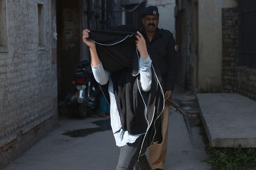 British prisoner Khadija Shah, who has been convicted of attempting to smuggle narcotics, covers her face with a garment as she walks past photographers after a court hearing in Rawalpindi on March 18, 2014. -- PHOTO: AFP