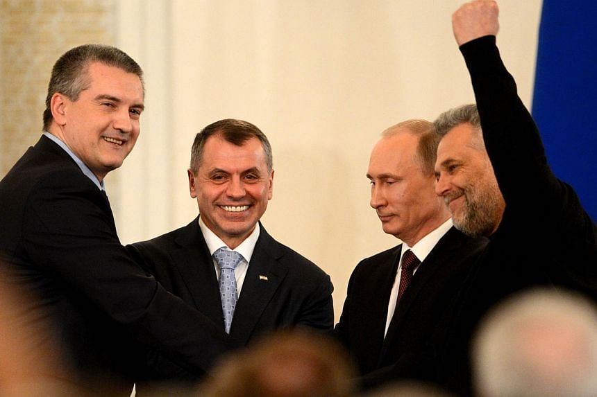 Russia's President Vladimir Putin (second right), Crimean Prime Minister Sergei Aksyonov (left), Crimean parliament speaker Vladimir Konstantinov (second from left) and Alexei Chaly, Sevastopol's new de facto mayor (right), join hands after signing a