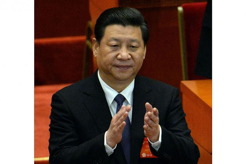 Chinese President Xi Jinping applauds at the closing session the National People's Congress (NPC) at the Great Hall of the People in Beijing on March 13, 2014.Chinese President Xi Jinping urged rural officials on Tuesday, March 18, 2014, to mak