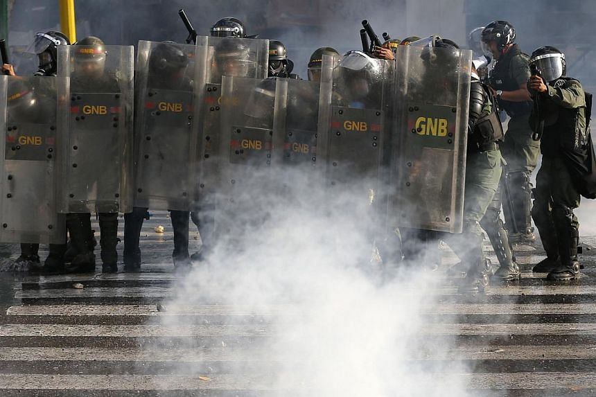 National Guards advance on anti-government protesters during clashes with police at Altamira square in Caracas on March 16, 2014. -- PHOTO: REUTERS