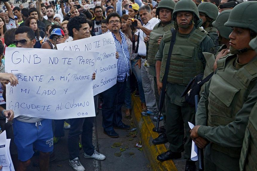 Demonstrators hold signs reading GNB don't stand in front of me, stand by my side and shake the Cuban in front of National Guard members at opposition stronghold Altamira square in Caracas on March 17, 2014. -- PHOTO: AFP