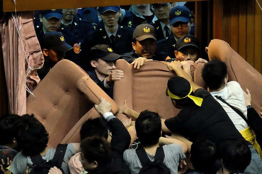 Activists occupy the Taiwanese Parliament in Taipei early on March 19, 2014 to protest moves by the ruling Kuomintang party to ratify a contentious trade agreement with China. -- PHOTO: AFP