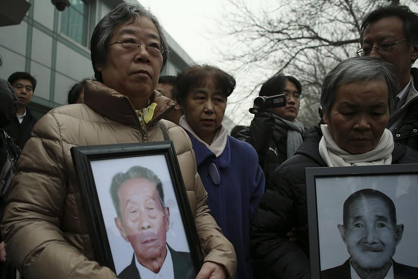 Relatives hold portraits of Chinese victims of forced labour during World War Two, as they stand outside a court in Beijing on Feb 26, 2014. -- FILE PHOTO: REUTERS