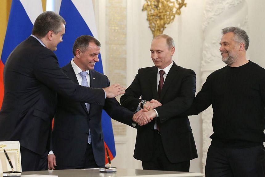 Russia's President Vladimir Putin (2nd right), Crimean Prime Minister Sergei Aksyonov (left), Crimean parliament speaker Vladimir Konstantionov (2nd left) and Alexei Chaly, Sevastopol's new de facto mayor (right), join hands after signing a treaty on