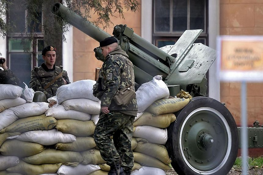 Ukrainian soldiers stand guard inside the navy headquarters in Simferopol on March 18, 2014. Pro-Russian forces used a tractor to ram through the gate of a Ukrainian navy base in western Crimea on Wednesday, March 19, 2014, seizing control of the ent