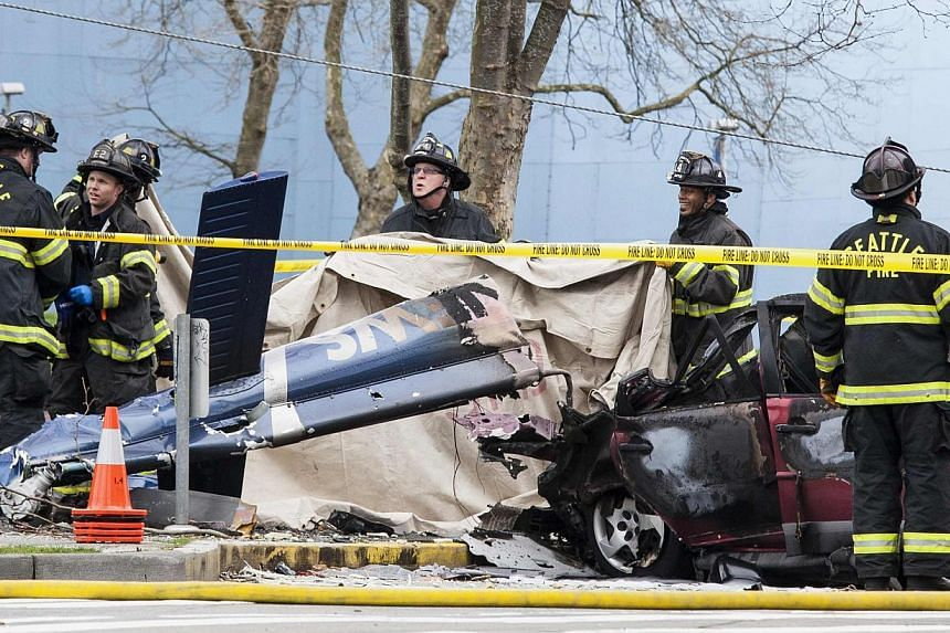 Firefighters investigate the crash of a Komo News helicopter, which killed Komo news photographer Bill Strothman and pilot Gary Fitzner near the Space Needle in Seattle, Washington, on March 18, 2014. -- PHOTO: REUTERS