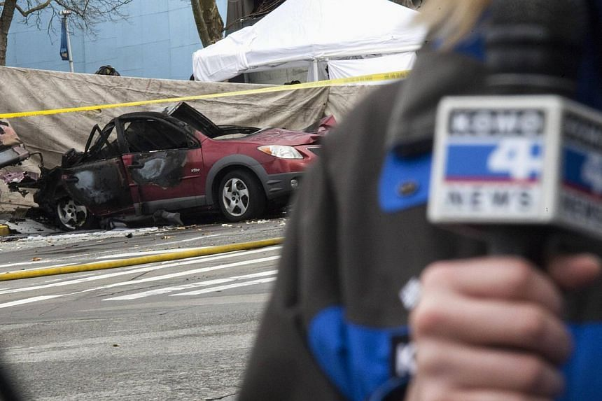 A Komo news reporter speaks on camera near the wreckage of a crashed Komo news helicopter and a car by the Space Needle in Seattle, Washington, on March 18, 2014. -- PHOTO: REUTERS