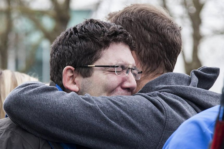 Komo news photographer Peter Mongillo gets a hug while covering the crash of his own news station's helicopter, which killed Komo news photographer Bill Strothman and pilot Gary Fitzner near the Space Needle in Seattle, Washington, on March 18, 2014.