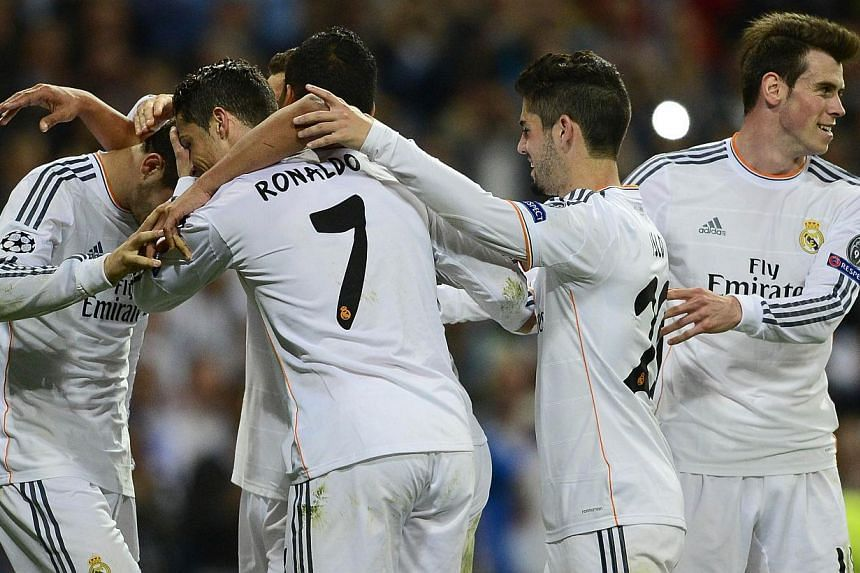 Real Madrid players celebrate after scoring their third goal during the Uefa Champions League round of 16 second leg football match Real Madrid vs Schalke 04 at the Santiago Bernabeu stadium in Madrid on March 18, 2014. -- PHOTO: AFP
