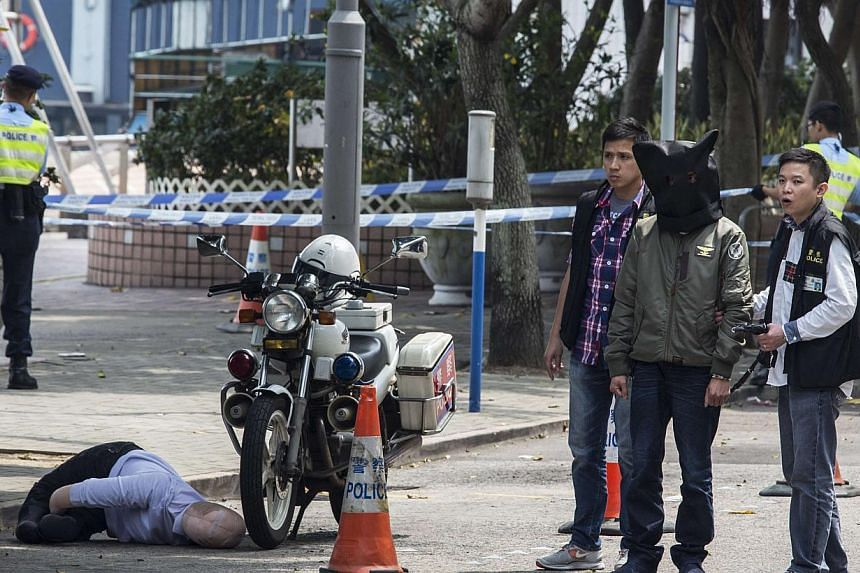 A suspect, seen walking next to a dummy of former Ming Pao chief editor Kevin Lau, is taken away by the police after the reconstruction of a crime scene at Sai Wan Ho in Hong Kong, March 18, 2014.Two Hong Kong media workers were attacked on Wed