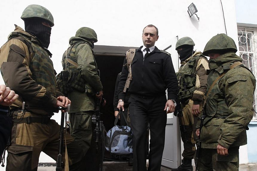 A Ukrainian naval officer passes by armed men, believed to be Russian servicemen, as he leaves the naval headquarters in Sevastopol, March 19, 2014.Pro-Moscow activists overran the Ukrainian navy's headquarters in Sevastopol on Wednesday with n