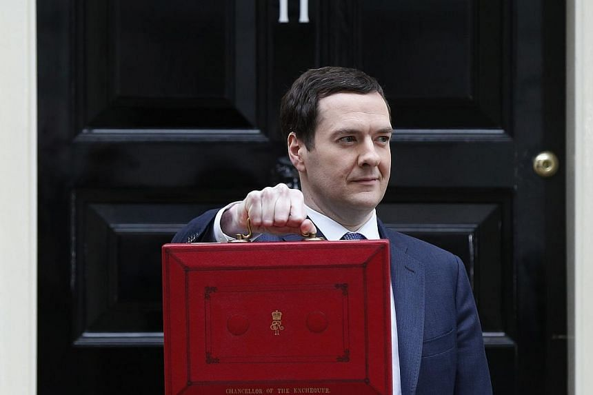 Britain's Chancellor of the Exchequer, George Osborne, holds up his budget case for the cameras as he stands outside number 11 Downing Street, before delivering his budget to the House of Commons, in central London on Wednesday, March 19, 2014.