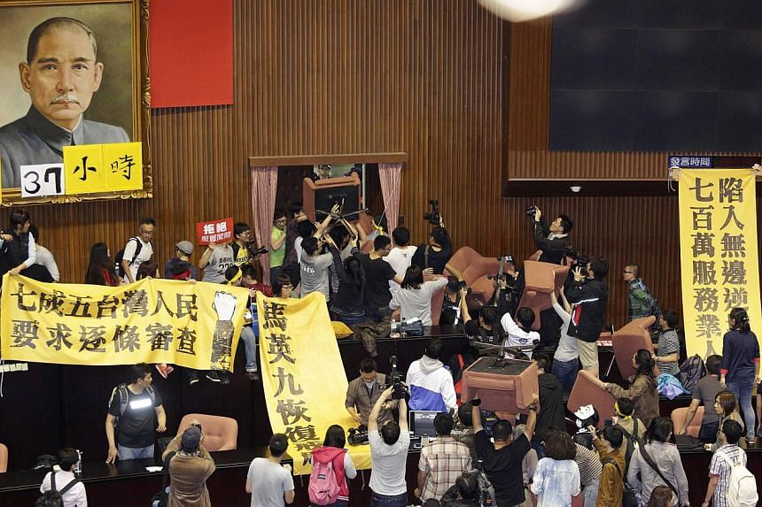 Students and protesters hold banners and chairs inside Taiwan's legislature in Taipei on March 18, 2014. -- PHOTO: REUTERS