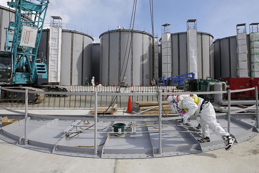 Men wearing protective suits and masks working on storage tanks for radioactive water at the tsunami-crippled Fukushima Daiichi nuclear power plant on March 10, 2014. TEPCO is struggling to handle a huge - and growing - volume of contaminated water a