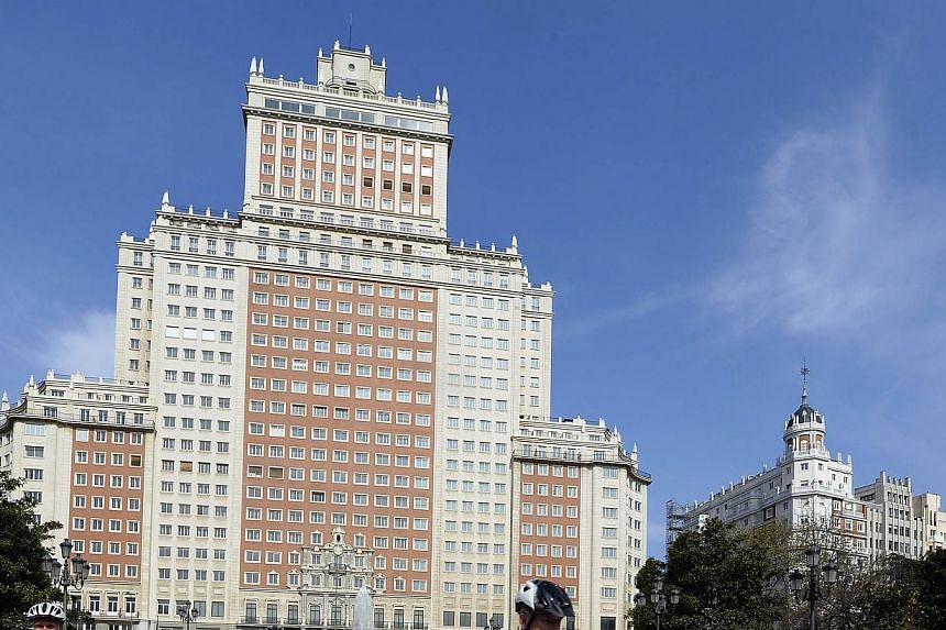 Visitors outside the historic Madrid skyscraper. Property magnate Wang Jianlin has offered 260 million euros (S$457 million) to the owner, Spanish banking giant Santander, to buy the 25-storey building. - PHOTO: AFP