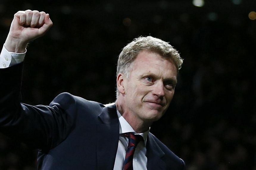 Manchester United's coach David Moyes celebrates as his team beat Olympiakos and reached the Champions League quarter-finals at Old Trafford in Manchester, northern England, on March 19, 2014. -- PHOTO: REUTERS