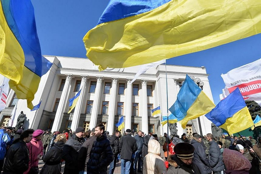People hold Ukrainian flags as they gather in front of the parliament in Kiev on March 17, 2014. Ukraine will not initiate a trade war with Russia and hopes to use the World Trade Organisation to resolve any such disputes initiated by Russia, Ukraine