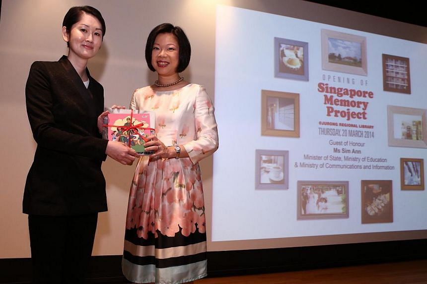 Ms Sim Ann, Minister of State for the Ministry of Communications and Information and Ministry of Education, receiving the token of appreciation from Mr Gene Tan, Director of the National Library. -- PHOTO: NATIONAL LIBRARY