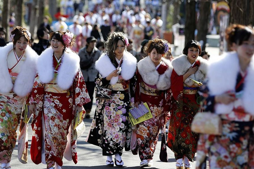Japanese women in kimonos attend a ceremony celebrating Coming of Age Day at an amusement park in Tokyo on January 13, 2014. The Coming of Age Day is one of fourholidays in Japan that was moved to a Monday to create a three-day weekend an