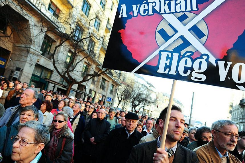 A participant holds a placard with a text 'Blood cries out! It was enough', in front of the local synagogue of Budapest on March 19, 2014 during a commemoration of the victims of Nazis occupation. -- PHOTO: AFP
