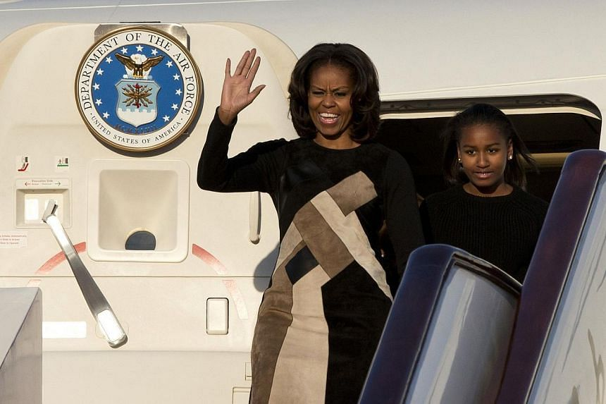 US First Lady Michelle Obama (left) waves as she and her daughter Sasha (right) leave their plane upon arrival at Beijing's Capital International Airport on March 20, 2014. Obama arrived in Beijing on Thursday evening, March 20, 2014, the o