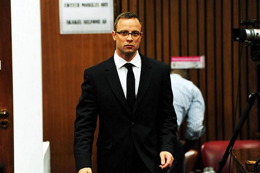 South African Paralympic athlete Oscar Pistorius (right) walks on the thirteenth day of his trial for the murder of his girlfriend Reeva Steenkamp at the North Gauteng High Court in Pretoria on March 19, 2014. Pistorius plans to sell the upmarke