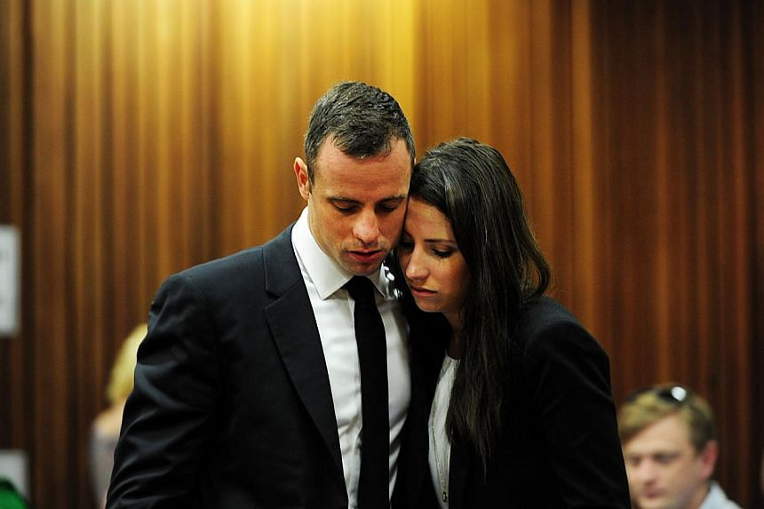 South African Paralympic athlete Oscar Pistorius with his sister Aimee on the thirteenth day of his trial for the murder of his girlfriend Reeva Steenkamp at the North Gauteng High Court in Pretoria on March 19, 2014. -- PHOTO: AFP
